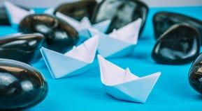 Van het de bootlood van het leidings Witboek de verdere schepen tussen abstracte rotsstenen op blauwe achtergrond Lichte Bezinnin Royalty-vrije Stock Foto