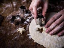 Van het de handgebruik van de gebakjechef-kok de scherpe vorm om Koekjesdeeg op keuken te snijden royalty-vrije stock afbeeldingen