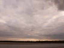 Van het de hemelvallen van de avond van de ebzomer grijze de wolkenstemming en rood met riv stock foto's