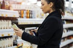 Van het de streepjescodescanner en aftasten van de vrouwenholding producten in winkel stock foto's