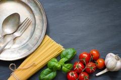 Van het de tomatenknoflook van het deegwarenbasilicum het voedsel abstract concept als achtergrond op zwart marmer Royalty-vrije Stock Afbeeldingen