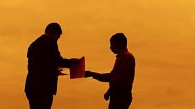 Van het de zonsondergangsilhouet van de zakenmanbespreking concept van het het zonlicht het kwade chef- bevindende klembord twee  stock footage
