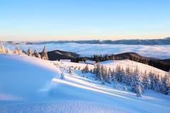 Van het gazon met geweven sneeuwbanken is er een mening aan de winterlandschap, eerlijke bomen in sneeuw, oude hutten, hooggeberg Stock Afbeelding