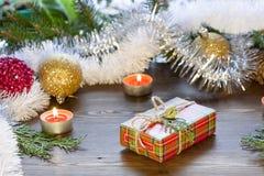 Van het Kerstmisnieuwjaar van de Kerstmisgift de decoratiemidden, vruchten en klatergoud in het licht van het branden van kaarsen Royalty-vrije Stock Fotografie