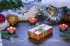 Van het Kerstmisnieuwjaar van de Kerstmisgift de decoratiemidden, vruchten en klatergoud in het licht van het branden van kaarsen Stock Fotografie