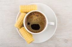 Van het koffiekop en wafeltje broodjes op schotel op houten lijst stock foto's