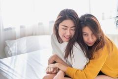 Van het lgbtpaar van Azië de de lesbische omhelzing en zitting op bed dichtbij witte windo Stock Fotografie