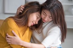 Van het lgbtpaar van Azië de de lesbische omhelzing en zitting op bed dichtbij witte windo Stock Afbeeldingen