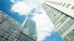 Van het tijd-tijdspanne de blauwe bewolkte gebouwen hemel witte glas stock footage