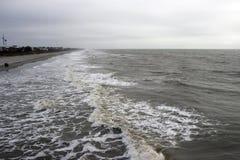 Van het Zuid- dwaasheidsstrand Carolina, 17 Februari, 2018 - mening van golven die binnen van de visserij van pijler rollen Stock Foto