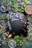 Van letters voorziend Aftreksel op donker bord Diverse verse kruiden, theehulpmiddelen en kop thee op donkere uitstekende achterg Stock Foto's