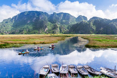 VAN LONG RESORT, NINHBINH, VIETNAM - SEPTEMBER 28, 2014 - Foreign tourists travelling on a traditional bamboo boat on the lagoon. stock photo
