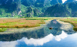 VAN LONG RESORT, NINHBINH, VIETNAM - SEPTEMBER 28, 2014 - Foreign tourists travelling on a traditional bamboo boat on the lagoon. royalty free stock photography