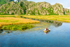 VAN LONG RESORT, NINHBINH, VIETNAM - SEPTEMBER 28, 2014 - Foreign tourists travelling on a traditional bamboo boat on the lagoon. Stock Images