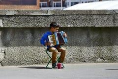 28 van Mei, 2015, Redactiefoto van bedelaars jonge jongen die op harmonika met zijn document plaing vormen geen de straat tot een Stock Foto