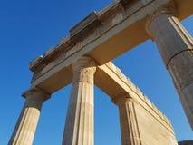 Van onderaan schot van verbazende kolommen van de antiquiteit geruïneerde bouw tegen duidelijke blauwe hemel op zonnige dag stock afbeeldingen