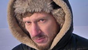 Van ontdekkingsreiziger op middelbare leeftijd in kap en laag wordt geschoten die koud en gefrustreerd close-up en vastbesloten o stock footage