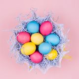 Van Pasen - nestelen de gele en rode eieren feestelijke als achtergrond in blauw document hooi op pastelkleur roze achtergrond, h Stock Afbeeldingen
