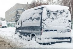 Van on a street covered with big snow layer.