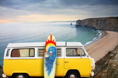 Van and surf board at a beach. A yellow van with a surf board at the beach Stock Images