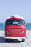 Van with surf board on the beach. Closeup of a front view of a red and white classic van with a surfboard on the top on the beach - useful as a surf background Royalty Free Stock Photo