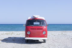 Van and surf board on the beach. Front view of a red and white classic van with a surfboard on the top on the beach - useful as a surf background Stock Image