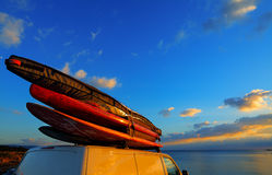 Van with surfboards on the roof. At sunset Stock Photos
