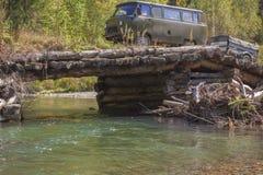 Van SUV avec une remorque sur un pont de rondin par la rivière de forêt Photo libre de droits