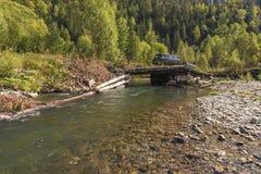 Van SUV met een aanhangwagen op een logboekbrug door de bosrivier Royalty-vrije Stock Foto's