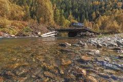 Van SUV met een aanhangwagen op een logboekbrug door de bosrivier Stock Fotografie