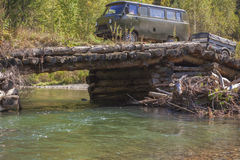 Van SUV with a trailer on a log bridge through the forest river Royalty Free Stock Photo