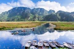 VAN TĘSK UCIEKAJĄCY SIĘ, Cudzoziemscy turyści podróżuje na tradycyjnej bambusowej łodzi na lagunie NINHBINH WIETNAM, WRZESIEŃ - 2 Zdjęcie Stock