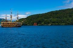 Van toeristenkruiser en vermiljoenen Torussenpoort op Ashi-meer, Hakone stock foto