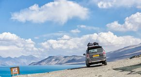 The van is parked beside the lake pangong royalty free stock photography