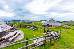 Van velikaplanina van Slovenië het grote plateau, landbouwweiland dichtbij stad Kamnik in Sloveense Alpen Blokhuizen op groen lan stock foto's