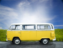 Van vintage yellow. A yellow volks wagen retro van.  The bus is on an asphalt surface with grass and sky background Royalty Free Stock Photo