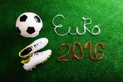 Van voetbalbal, cleats en Euro 2016 teken tegen kunstmatig gras Stock Foto
