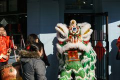 VANCÔVER, CANADÁ - 18 de fevereiro de 2014: Os povos em Lion Costume branco no ano novo chinês desfilam no bairro chinês de Vancô Fotografia de Stock