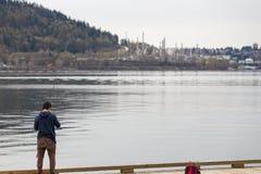 VANCÔVER NORTE, BC, CANADÁ - 9 DE ABRIL DE 2018: A refinaria do Parkland na montanha de Burnaby, com um homem que está em uma doc foto de stock royalty free