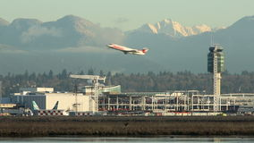 Vancouver Airport, Small Jet Take Off. A small jet takes off at Vancouver International Airport, YVR, with the Coast Mountains in the background and the Fraser stock video