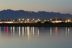 Vancouver Airport YVR, British Columbia. Vancouver International Airport, YVR, at dusk reflecting in the calm waters of the Fraser River. The Coast Mountains Stock Photos