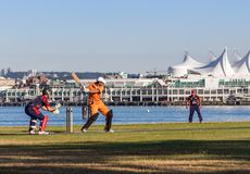 VANCOUVER, AVANT JÉSUS CHRIST, CANADA - 19 JUILLET 2015 : Les jeunes hommes jouent au cricket sur un champ devant l'endroit de Ca photos stock