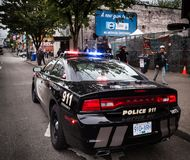 VANCOUVER, BC, CANADA - MAY 11, 2016: VPD cruiser on Vancouver`s Downtown Eastside with officers in the background. Dealing with an issue royalty free stock photo