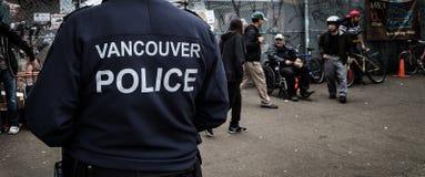 VANCOUVER, BC, CANADA - MEI 11, 2016: De Politieman van Vancouver op patrouille op een gebied van zware druggebruik en armoede da stock foto's