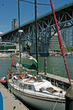 Vancouver BC, Canada. Sail boat under the Burrard Bridge, entrance to False Creek Public Marina, Vancouver BC. Granville Island is on the left across the water royalty free stock image