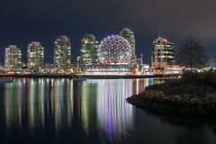 VANCOUVER, BC, CANADA - 19th November 2016: Geodesic Dome of Van. Couver World of Science shines brightly over the water with modern office and residential stock images