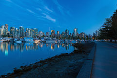 Vancouver BC Skyline along Stanley Park Seawall in Canada. Vancouver British Columbia Canada skyline by the marina along Stanley Park seawall during evening blue Royalty Free Stock Image