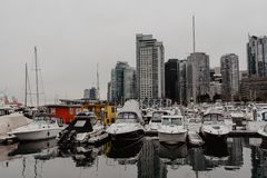 Vancouver, British Columbia/Canada - December 24 2017: waterfron. T in downtown with some boats and skyscrapers reflecting in the water. Cinematic film effect Stock Photography