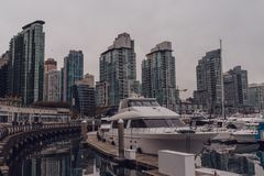 Vancouver, British Columbia/Canada - December 24 2017: waterfron. T in downtown with some boats and skyscrapers reflecting in the water stock photo