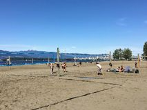 A group of people playing beach volleyball on a beautiful sunny day along the sandy beaches of Spanish Banks, in Vancouver, B.C. Vancouver, British Columbia stock images